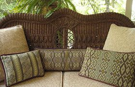A collection of Kilim patterns on a summer porch in soft sage greens from patterns in the cross-point TM collection