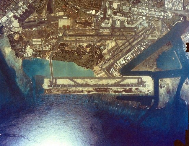 """Honolulu International Airport's reef runway; """"By the time it was finished more than 19 million cubic yards of dredged material had been used, pumped by three hydraulic suction dredges from four offshore borrow areas, to form the land mass.  An additional 800,000 tons of quarried stone and 18,100 four and six-ton dolosse concrete armor units comprise the protective structure separating the runway form the ocean."""""""