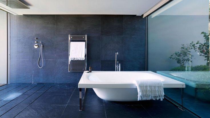 Bagno minimalista blu scuro e bianco portato ad un altro livello con con una splendida illuminazione naturale e vista esterna.