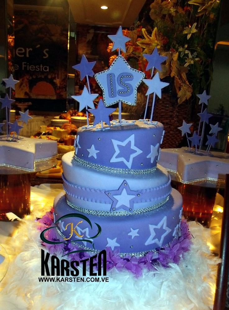 Torta de 15años inclinada color lila con estrellas que decoran la torta y detalles plateados. Con una base adorna con una boa de plumas color blanca