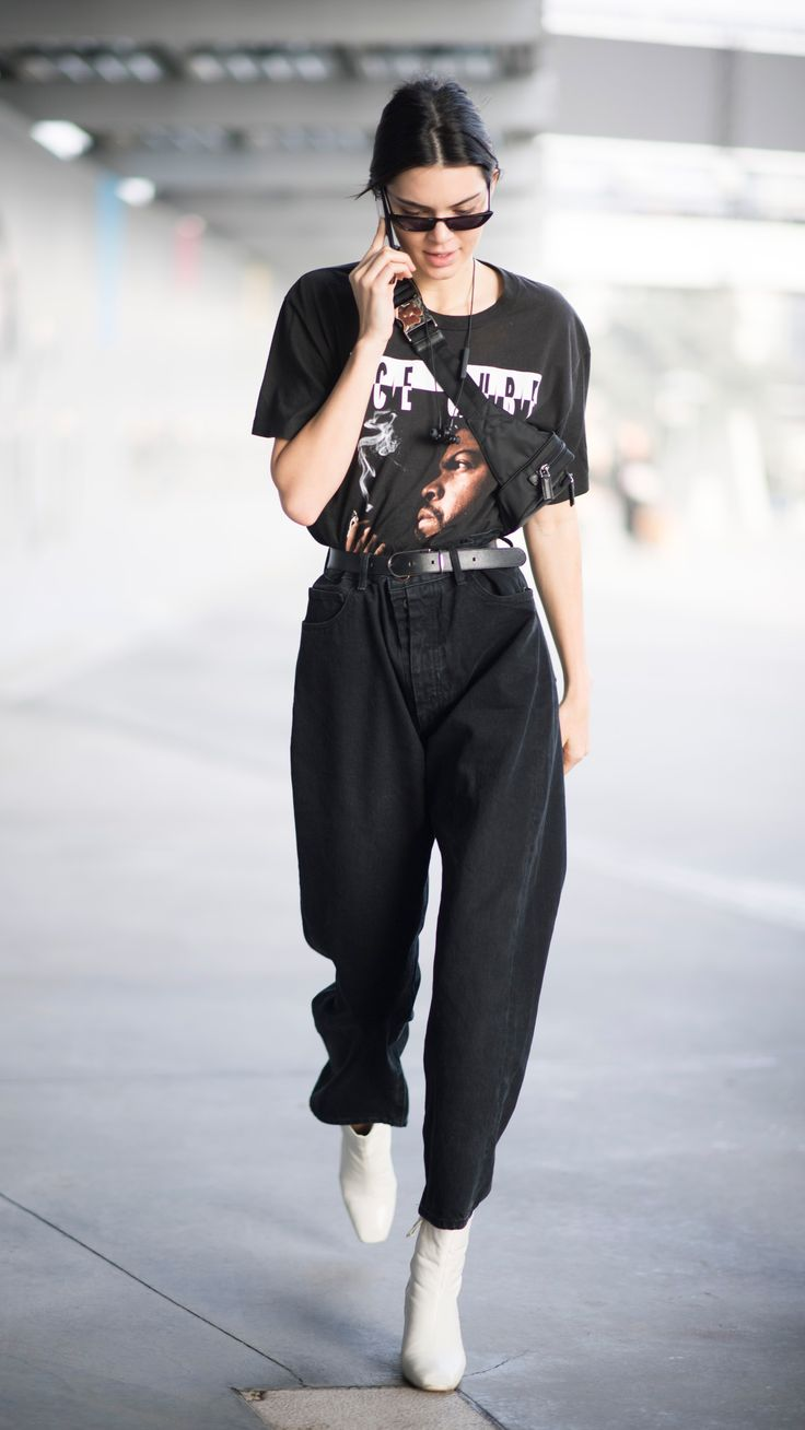 Today, Jenner tucked The Predator rapper's 1992 album merch into high-waisted black denim cinched with a leather belt for added so-bad-it's-good swagger. While her baggy button-fly jeans were worn in all their slouchy-cool glory, they were cropped at just the right place to put a pair of optic white leather Kurt Geiger booties on full display.