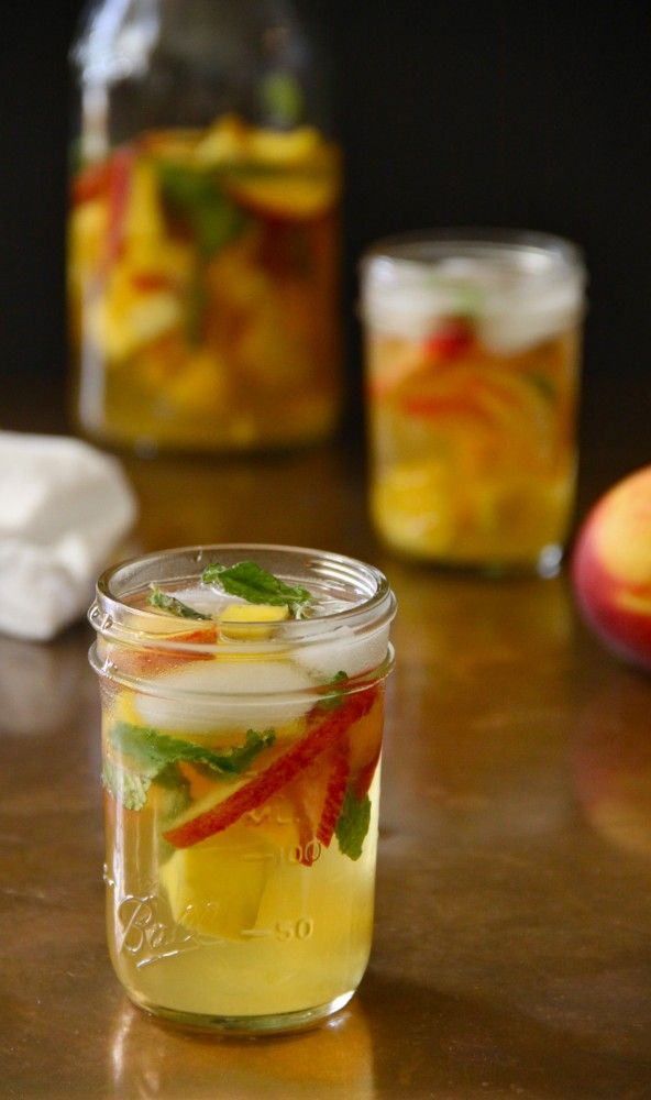 Mango, Mint, & Peach Sangria | Summer party drink | 1/4 cup fresh mint (plus more for garnish) 1 cup Grand Marnier 2 peaches, sliced thinly 1 bottle of Pinot Grigio 1/3 cup water 1 large fresh mango, chopped 1/3 cup granulated sugar