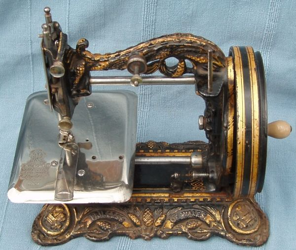 Princess of Wales: Serial No. 96544.   Another example of the Princess of Wales sewing machine. The cast details make it a very difficult machine to clean. The cloth plate is nickel plated which although it generally is in good condition it has suffered from corrosion particularly where the Trade Mark has been stamped into the plating and the base has lost some of its jappaning round the bottom recesses.