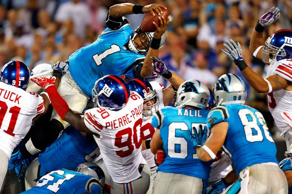 Cam Newton uses his height to his advantage and leaps over the line for a touchdown.