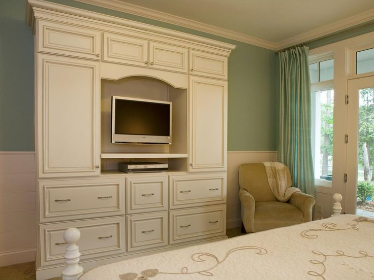 The elegant white armoire provides functional storage and doubles as a tv entertainment center for Master bedroom set with armoire