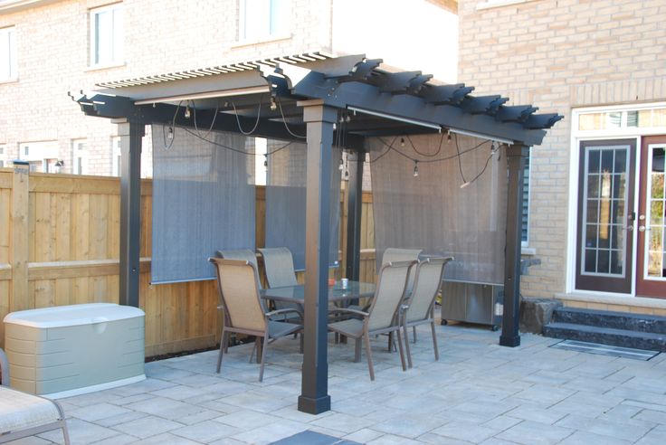 black pergola with customized top beams. Added gray Nesling Rollerblind on all sides for extra privacy.