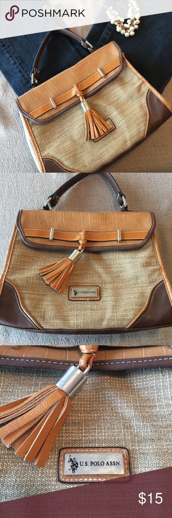 US Polo Assn handbag. Tassel, faux leather accent US Polo Assn handbag. Interior has two pocket and a zip pocket. Exterior has faux leather accents on a light tan tweed body. Magnetic closure. Tassel on closure with silver accents. Leather hand strap to carry. U.S. Polo Assn. Bags Satchels