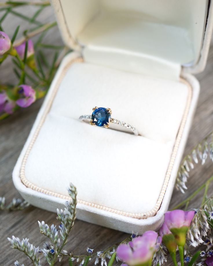 This two tone ring design harmoniously 'marries' white and yellow gold, complementing the beautiful deep blue color of the Montana Sapphire. The traditional diamond cut of the stone is perfectly set off by the glamorous claw prongs and hand set white diamond pavé. This ring will look lovely paired with either a Yellow or White Gold wedding band.  By S. Kind & Co.
