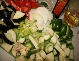 Vegetables in clay pot cooking.  Use squash, onions, eggplant, zucchini, tomatoes, bell peppers to make a tasty healthy vegetable bake.  This is a pretty table presentation too.