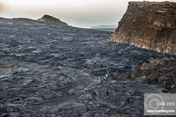 Tourists walking through lava field around the very active Erta Ale shield volcano, Danakil depression, Ethiopia, Africa