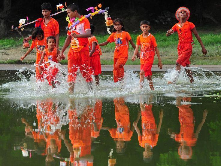 Woensdag 30 juli: Indiase kinderen waden door de ondergelopen straten van Allahabad nadat ze, ter ere van de maand van Shravan, de Ganges hebben bezocht