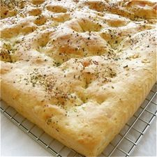 """no-knead garlic-cheese flatbread, King Arthur recipe  Stir up the batter for this easy yeast bread, scoop it into a 9"""" x 13"""" pan, and bake up a moist, golden flatbread, studded with melting cheese and chopped garlic. Serve it fresh; or let it rest overnight, then cut into strips and crisp in the oven, to make delightfully crunchy appetizer bread sticks."""