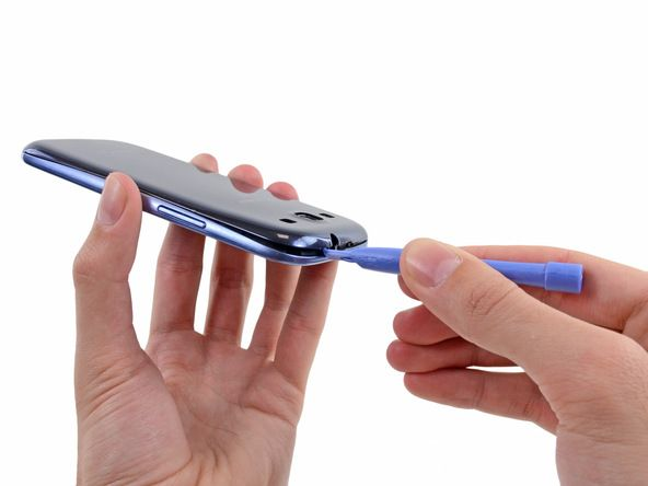 3. Deslice la herramienta de apertura Best 128 a la izquierda a lo largo del borde superior y repite el movimiento de giro para ampliar el espacio entre la carcasa trasera y el teléfono.