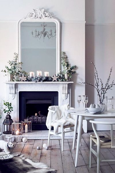 White on white decor with simple holiday/Christmas decorations on a classic fireplace mantel