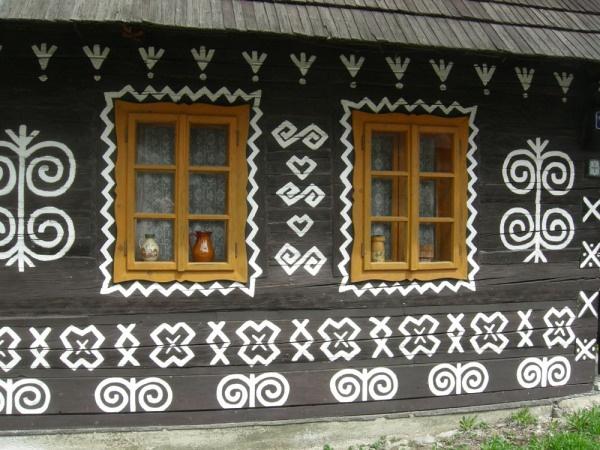 Na fotografii Andrzeja Chlebickiego: drewniany dom z wioski Cicmany na Słowacji (okolice Ziliny) – motywy zdobnicze łączące elementy roślinne z bardzo starą magią kobiecą.
