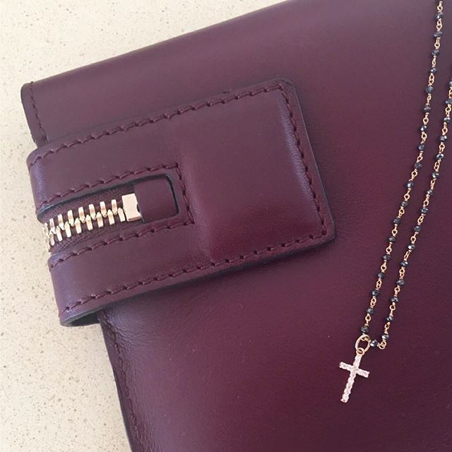 NIVES I Rosary collection 18k light rosé gold tiny black diamond bead necklace with white diamond cross pendant. Style: Victoria Beckham bordeaux leather clutch