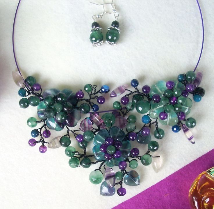 """Cercei şi colier """"Tristeţi în valuri risipite"""" din colecţia de fluorit """"Flori de piatră Bijoux"""" Didina Sava . Colierul este confecţionat din inimioare de fluorit verde marin, petale de fluorit cu inserţii mov, mărgele de agate dantelă, mărgele de ametist, sârmă modelatoare argintată neoxidabilă şi neagră, pe un suport de oţel siliconat.  De vânzare"""