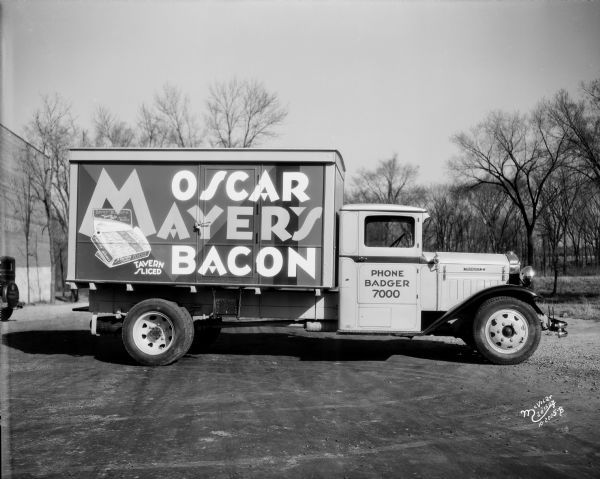 "Profile view of the right side of an Oscar Mayer bacon truck made by Diamond T parked near a building. The sign on the back of the truck reads: ""Oscar Mayer's Bacon"" and ""Tavern Sliced."" Photo from 1930. Image ID: 19872"