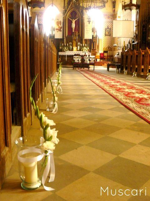 świece w szklanych lampionach ozdobionych kwiatami tworzą alejkę ślubną w kościele