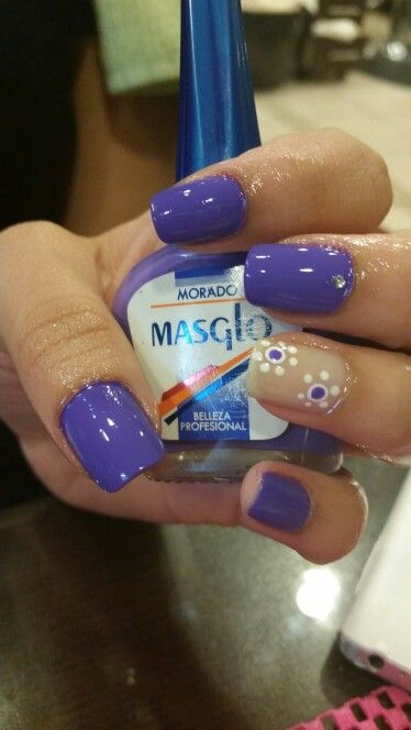 Purple painted nails with white and purple dots on party nail. #DIYNailArtDesigns