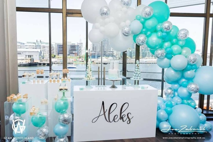 Event theme in baby blue, turquoise and silver. Gorgeous balloon arch, Perspex stand / boxes and dessert table