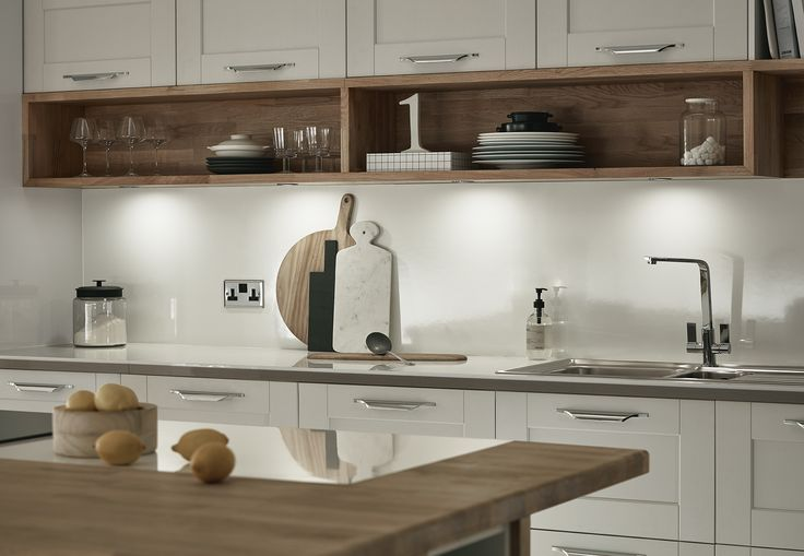 Bespoke shelving is a perfect way to add a unique twist to your kitchen. As seen with our Fairford Kitchen in Dove Grey - consider warming up this neutral grey with some custom-made solid oak shelving under your wall units. For more information, visit Howdens.
