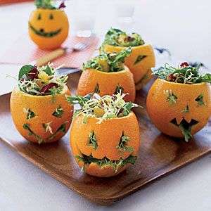 Mesclun Meanies  Cut a jack-o'-lantern face on each orange.  Whisk together reserved orange zest and juice with vinegar, maple syrup, mustard, lemon juice, ginger, pepper and salt. Whisk oil in until combined.  Toss greens and reserved orange pieces with 2 to 3 Tbsp. dressing. Stuff orange shells with salad; top with pumpkin seeds.