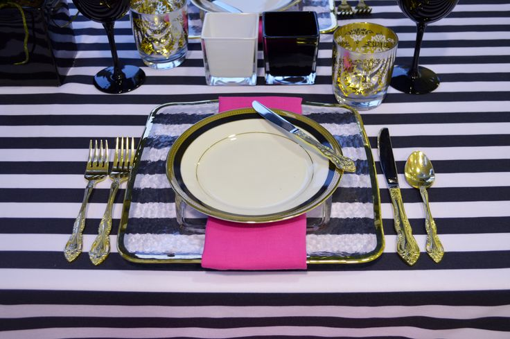 White & Black Striped Linen Topper, Glass Square Charger with Gold Rim, Napoleon Dessert Plate, Fuschia Hemstitch Napkin, Regal Gold Flatware, Silver & Gold Brocade Double Old Fashioned Glass, Black Wine Goblet & Black & White Glass Urban Cubes   Chair-man Mills.