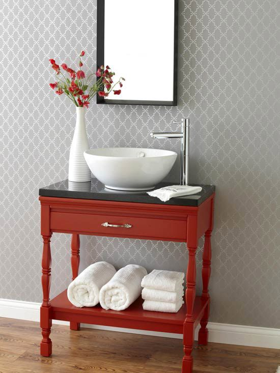 This end table converted into an open vanity is perfect for a small bath. The polished countertop, vessel sink, and sleek faucet bring fresh design to limited quarters, while playfully contradicting the traditional base. The shelf below adds space to keep extra towels on hand.
