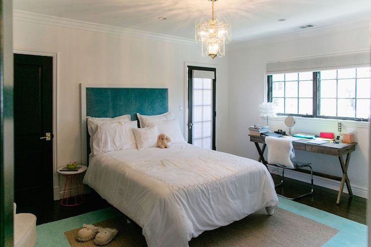 Contemporary kid's room features an art deco chandelier hanging over a white framed peacock blue headboard on full bed dressed in soft white bedding paired with one single nightstand atop a small jute rug layered over a larger turquoise rug.