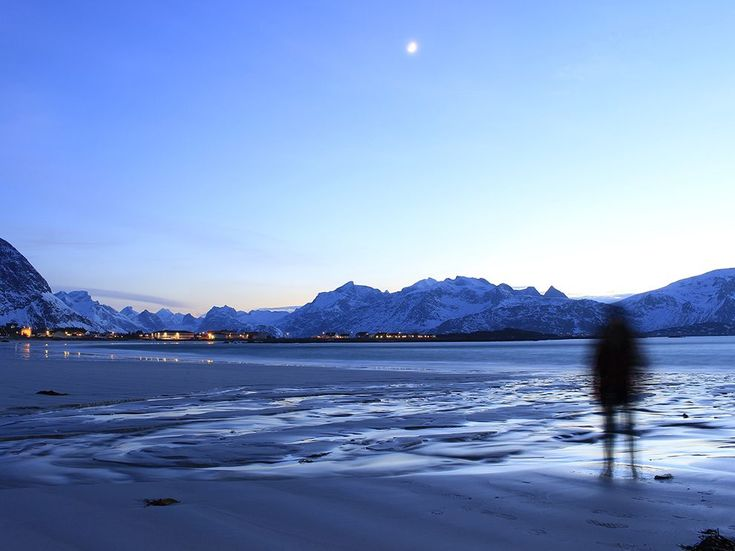 Duine ag seasamh ar trá san Iorua. Picture of a person on a beach in Lofoten Islands, Norway
