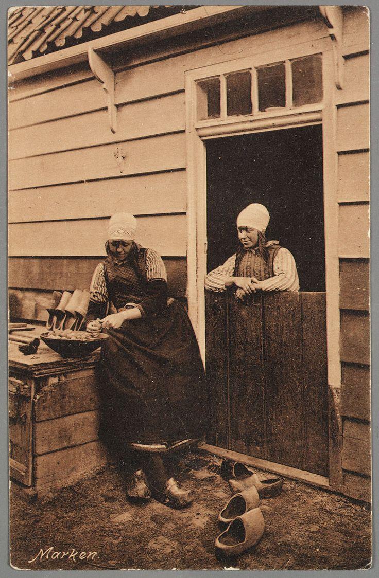 Een vrouw in dracht leunt op een onderdeur en kijkt naar een vrouw die aardappelen schilt, zittend op een houten kist, mogelijk een kippenhok.  Ze dragen beiden een hoge kap. 1910-1917 #NoordHolland #Marken