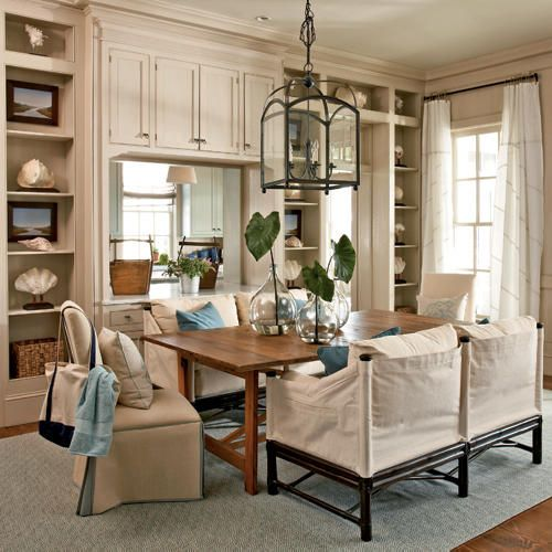 Informal meets formal in this dining area, where a pair of casual settees provides contrast to the more-traditional upholstered slipper chairs. Find the clam shell and nautilus sculptures seen on the book shelves at seasideinspired.com/beach_style_sculptures.htm