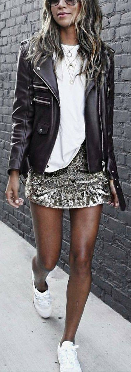 Black leather jacket over white top with metallic silver mini skirt.