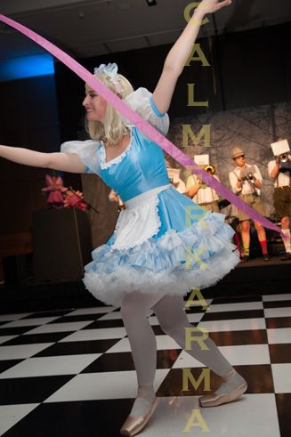 Alice Ribbon Dancer in ALICE IN WONDERLAND UK CHOREOGRAPHED THEATRICAL SHOW - with the famous faces of  White Rabbit, Tweedle Dum and Tweedle Dee, and spectacular marching band creating an Alice In Wonderland twist.   Tel: 020 3602 9540  UK Entertainment Agency http://www.calmerkarma.org.uk/Alice-in-Wonderland.htm