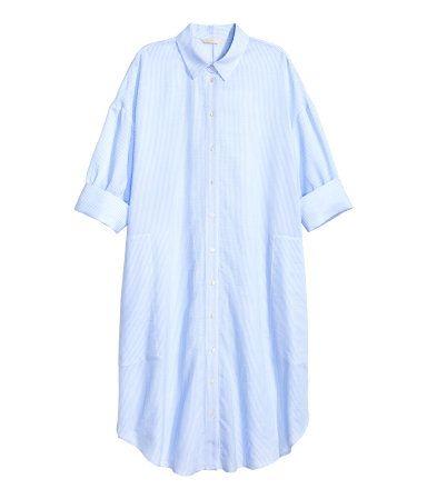 Hellblau/Gestreift. Blusenkleid aus weichem Baumwollstoff. Das Kleid hat überschnittene Schultern und kurze Ärmel mit breitem, fixiertem Umschlag.