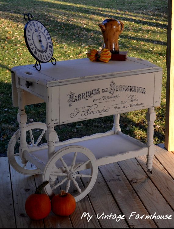 This is an antique tea cart, possibly the sweetest and most charming decorative piece ever! Painted in Old White, stenciled in fancy French typography, distressed and finished with Polycrylic! Dimensions are 29 high x 18 deep (with drop leaf down) and 35.5 deep (with drop leaf up) x 34 Long. It is absolutely ONE OF A KIND and absolutely lovely! We ship this item via FedEx Ground services, item will ship within 1 week of purchase date! SHIPPING IS INCLUDED IN THE PRICE