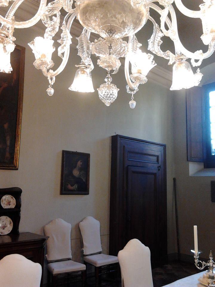 Palazzo Monti della Corte - In fondo all'atrio c'è il grande portone da cui un tempo entravano le carrozze, alla base della volta si possono ammirare gli stemmi affrescati delle famiglie legate al casato, qui due porte conducono all'ampia sala da pranzo, la Sala Rossa, con un bel camino in marmo nero del Belgio e un grandissimo lampadario di Murano.