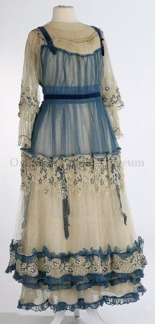 1912-1916 white and blue multi-layered dress made from different types and sizes of netting; 3/4-length sleeves. Dress trimmed with blue embroidered netting and blue velvet ribbons over the shoulders, at the waist, and on the underskirt.