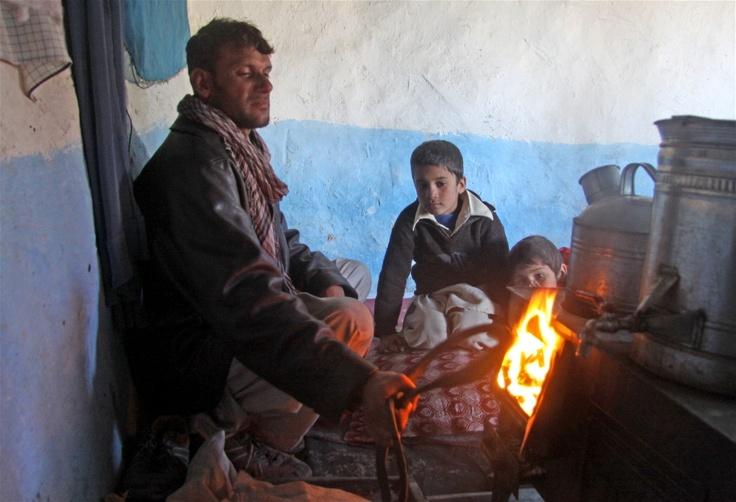 A returnee family keeps warm by burning plastic waste in their Bukhari (wood heater) in their mud-hut east of Kabul, Afghanistan