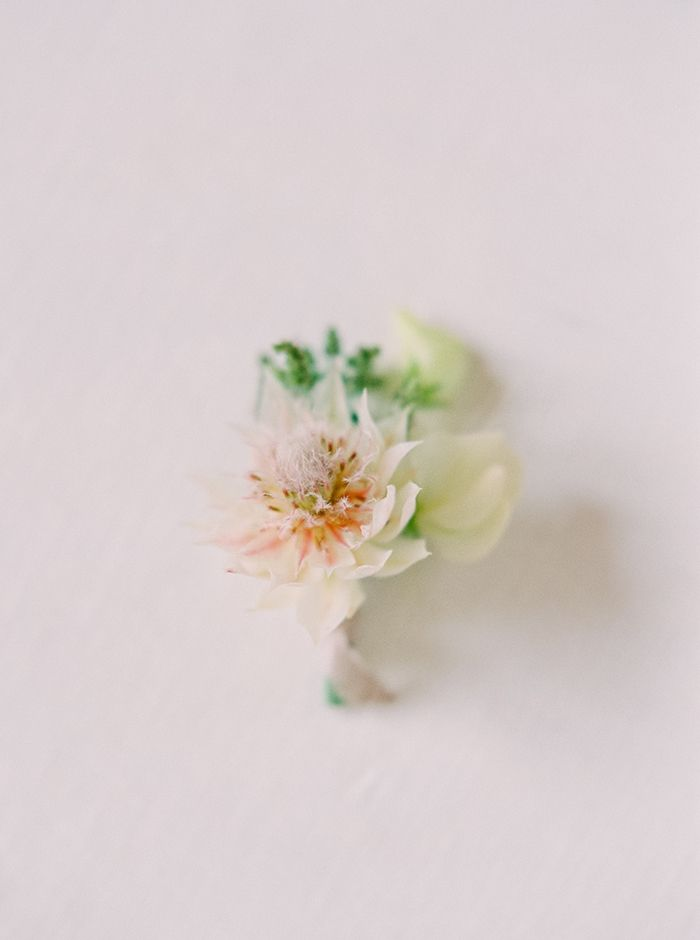 A delicate boutonniere in whites and blush.