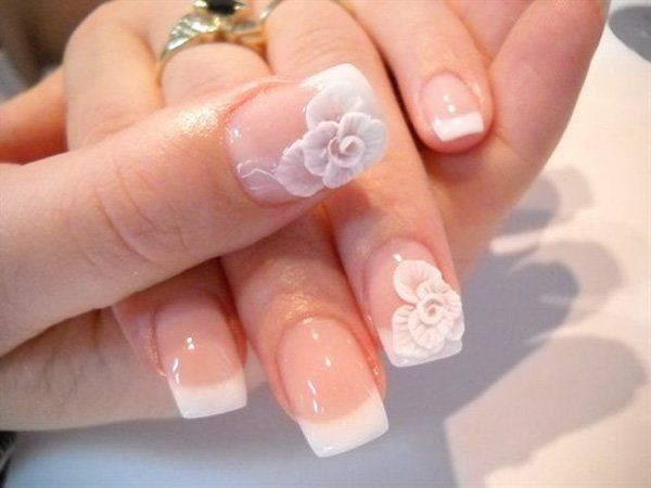 Amazing almost 3D inspired floral French tips. The nails are coated in clear polish for the base and tipped with plain white polish. A seemingly huge white rose is also painted on top as if to look like it's growing right out of your nails.