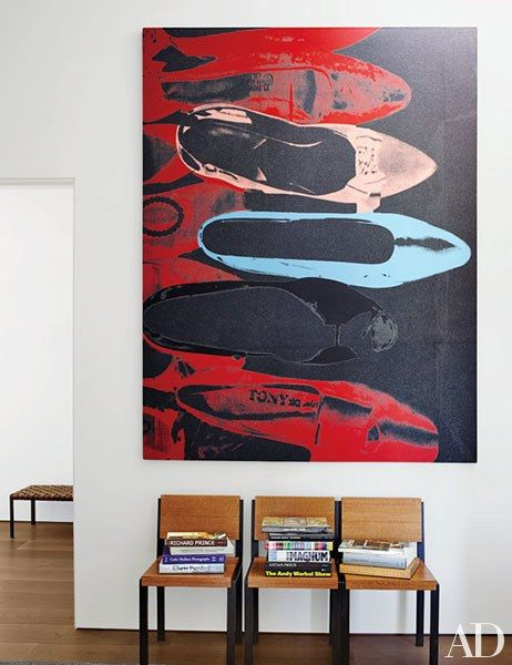 A work by Andy Warhol is mounted above a trio of vintage chairs at the entrance to the master bedroom | archdigest.com