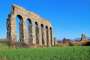 Arches of an ancient Roman aqueduct, made of blocks of tufa. A path runs along the property in a green park in the outskirts of Rome. Ancient Ancient Civilization Arch Architecture Building Exterior Built Structure Culture Historic History Old Old Ruin Outdoors Ruined Travel Travel Destinations