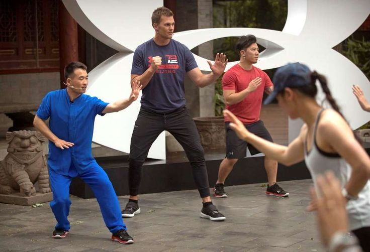 New England Patriots quarterback Tom Brady, center, practices a martial-arts technique - Mark Schiefelbein/AP