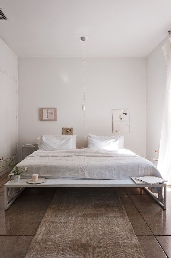 LOVE THIS!! A small bedroom made to look bigger and airy by placing a low bed and hanging low the art on the wall. More tricks used here- Using light colors and a low-hanging light bulb which emphasizes the height of the ceiling. Expert Advice: 11 Tips for Making a Room Look Bigger @ Remodelista