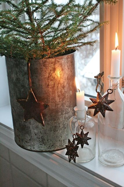 Rustic country holiday vignette with glass bottles, white candles, stars, and evergreens.