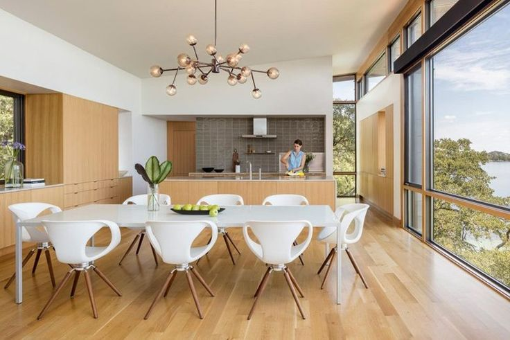Dining room and kitchen with plate glass window, white dining room table and chairs.