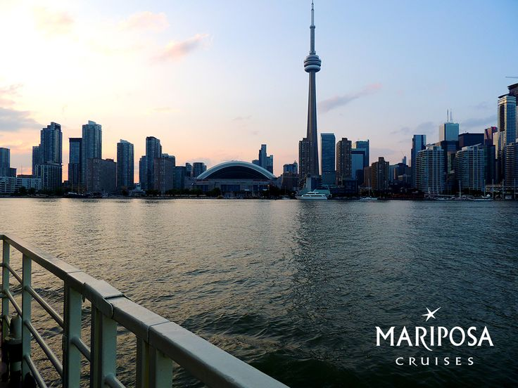 View of the sun setting behind the Toronto city skyline from the deck of Mariposa Cruises Showboat.