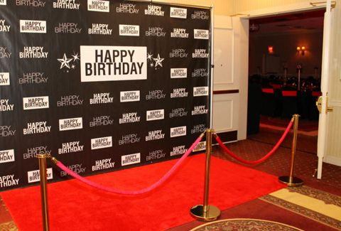 Red carpet birthday entrance. Matte vinyl step & repeat, generic happy birthday design, brass stanchions, velvet red velour ropes, paparazzi style photography. Was held in Clifton Park, NY at the Comfort Inn Suites.